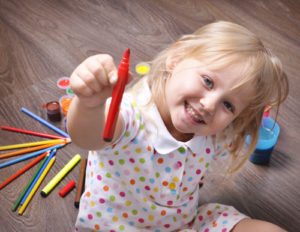 Young girl playing with art supplies